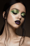 Beautiful girl with spring green makeup and vampire lips. beauty face. Photos shot in studio Royalty Free Stock Photography