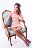Beautiful girl in the Spring image sits on a chair in baroque st. Portrait of curly brunette with purple make-up in pink dress with soutache technique Royalty Free Stock Photo