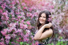 Beautiful girl in spring park with flowers. Lifestyle portrait, happy woman with blooming cherry tree. Skin care and beauty. Smiling teen girl in spring garden Royalty Free Stock Photos