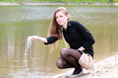 Beautiful girl and spring at the river. Beautiful girl in the spring of the river, from the hands of flowing water Royalty Free Stock Images