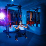 Beautiful girl squats with barbell Royalty Free Stock Photo