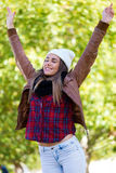 Beautiful girl standing in autumn field with arms raised. Royalty Free Stock Image