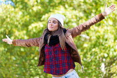 Beautiful girl standing in autumn field with arms raised. Royalty Free Stock Images