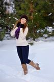 Beautiful girl standing on background winter trees Stock Photo