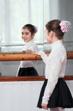 Girl standing at barre and looks through mirror Royalty Free Stock Photo