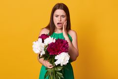 Beautiful girl standing with bouquet of burgundy and white peonies in her hands, wearing green sundress, posing with open mouth, royalty free stock photos
