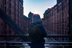 Back girl view. Girl standing on the bridge watching the modern building the sunset and soft light. Hamburg, hafencity royalty free stock photos