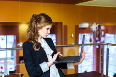 Beautiful girl standing in a cafe and working on laptop Stock Images