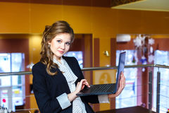 Beautiful girl standing in a cafe and working on laptop Royalty Free Stock Photos