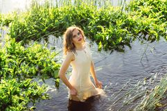 Beautiful girl standing in the center of the river. And looking to camera royalty free stock photography