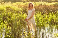 Beautiful girl standing in the center of the river and squeeze the dress. Beautiful girl standing in the center of the river and squeeze the white dress stock photo