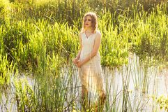 Beautiful girl standing in the center of the river and squeeze the dress stock photo
