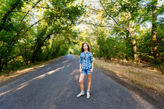 Beautiful girl standing on an empty road between green trees Royalty Free Stock Photos