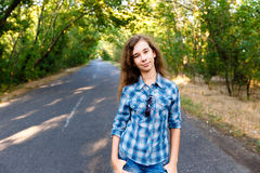 Beautiful girl standing on an empty road between green trees Stock Photos