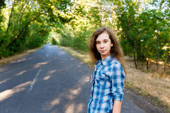 Beautiful girl standing on an empty road between green trees Royalty Free Stock Photo
