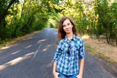 Beautiful girl standing on an empty road between green trees. Beautiful girl in blue plaid shirt standing on an empty road between green trees Royalty Free Stock Image
