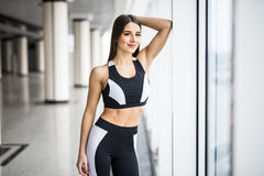 Beautiful girl standing in the gym at the window Stock Photography