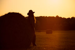 Beautiful girl standing near a hay bale in field. Stock Photos