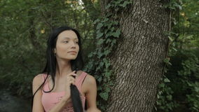 Beautiful girl standing near the tree in the stock footage