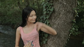 Beautiful girl standing near the tree in the stock video