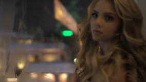 Beautiful girl standing near a window in the evening stock video footage