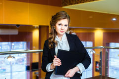 Beautiful girl standing in a office and holding a laptop Royalty Free Stock Images