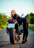 Beautiful Girl standing with a red motorcycle Royalty Free Stock Photo