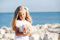 Beautiful girl standing on rocky seashore Royalty Free Stock Images