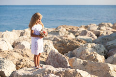 Beautiful girl standing on rocky seashore Royalty Free Stock Photo