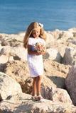 Beautiful girl standing on rocky seashore Stock Photo