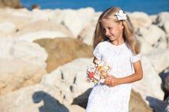 Beautiful girl standing on rocky seashore Stock Image