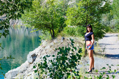 Beautiful girl standing on the shore of a mountain river Stock Photo