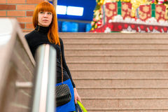 Beautiful girl standing on the stairs with bags. In the mall Royalty Free Stock Image