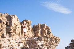Beautiful girl standing at the stony wall Stock Images