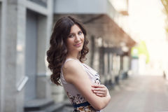 Beautiful girl standing on the street near the house Stock Photos