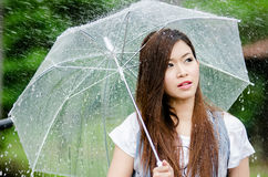 Beautiful girl is standing with umbrella  among rain Royalty Free Stock Photo