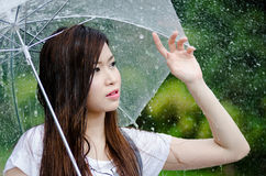 Beautiful girl is standing with umbrella  among rain Royalty Free Stock Photography
