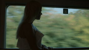 Beautiful girl standing by the window of the train stock video