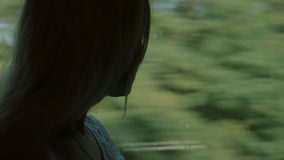Beautiful girl standing by the window of the train stock footage