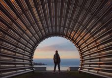 Beautiful girl stands in the arch of the pipe lines Stock Images