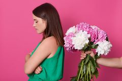 Beautiful girl stands backwards to unknown faceless person who give her peonies  over yellow studio background. Young. Offended woman refuses from flowers from royalty free stock photo