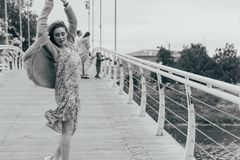 Beautiful girl stands on the bridge, the wind blows in her face, developing her hair. girl smiles. dancing black and white photo stock photo