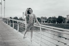 Beautiful girl stands on the bridge, the wind blows in her face, developing her hair. girl smiles. dancing black and white photo stock photos