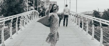 Beautiful girl stands on the bridge, the wind blows in her face, developing her hair. girl smiles. dancing black and white photo stock image