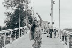 Beautiful girl stands on the bridge, the wind blows in her face, developing her hair. girl smiles. dancing black and white photo stock photography