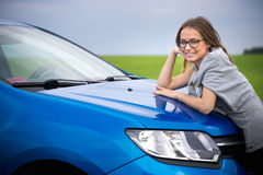 Beautiful girl stands by the car in the green field. Beautiful girl stands by the car in the green field Stock Photos