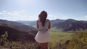 A beautiful girl stands on a cliff in the mountains and holds a bouquet with flowers. Beautiful landscape stock video footage