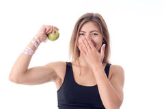 Beautiful girl stands directly and shows an apple in one hand  his biceps Royalty Free Stock Image