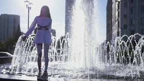 A beautiful girl stands on the edge of a fountain and is happily spinning. HD, 1920x1080. slow motion. stock video