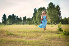 Beautiful girl stands on green field Stock Photography